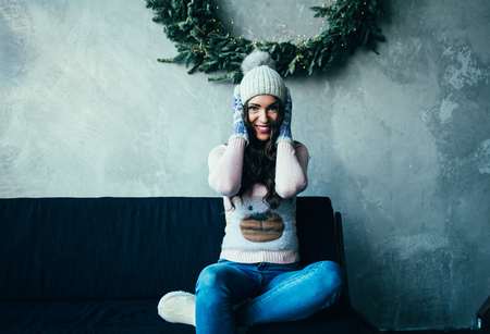 cheerful woman in hat and cozy clothes sitting on sofa and smiling