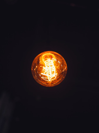 Light bulb on black background 스톡 콘텐츠
