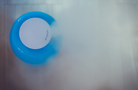 Air humidifier during work. The blue humidifier moistens dry air. Фото со стока