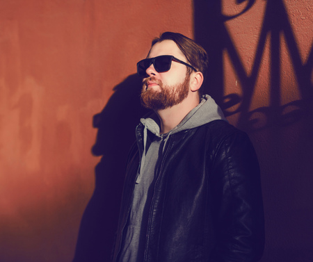 stylish bearded man in a leather jacket and sunglasses near the wall Stock Photo
