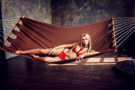 blonde lying on hammock in charming red lingerie indoors