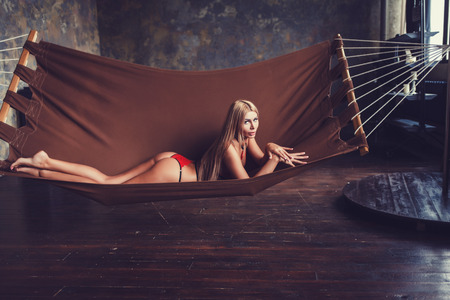 sexy woman lying on hammock wearing red lingerie