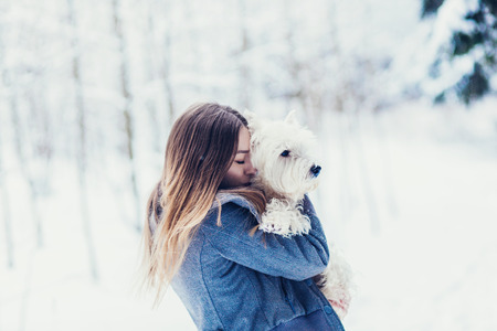 portrait of a woman hugging a dog in the winter forest. Concept of friendship and devotion