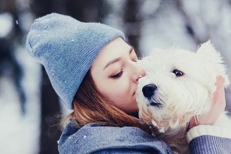 Portrait of beautiful young woman with dog in wintertime Stock Photo