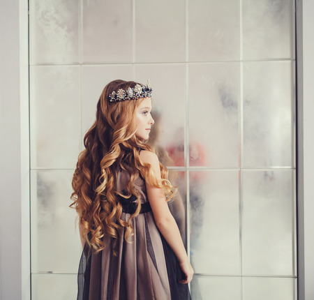 Beautiful little girl with long wavy hair wearing dress