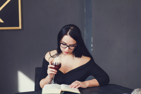 elegant lady in glasses with wine reading a book in a cafe