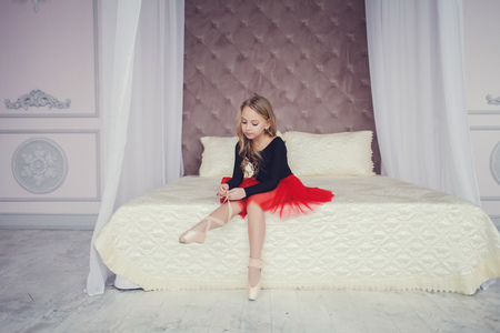 Little girl dressed as a ballerina in a tutu, tying her ballet slippers