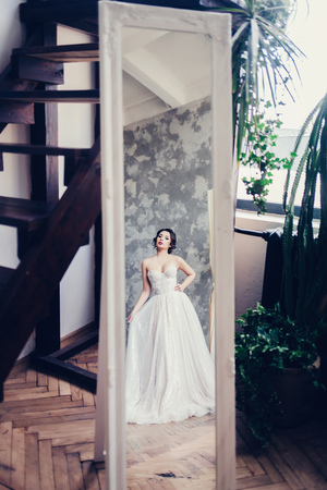 beautiful bride brunette looks in the mirror Stock Photo