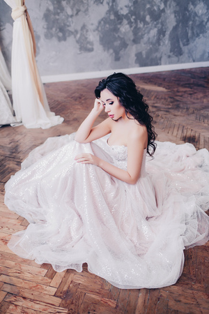 Pretty young bride in wedding dress with luxurious hair and makeup.