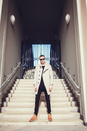 Attractive man in sunglasses and coat. Model, posing in urban style