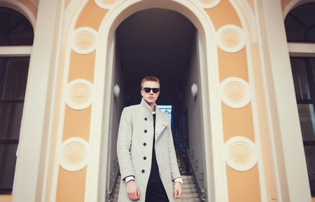 Fashionable man in coat and sunglasses posing in old city.Lifestyle Stock Photo