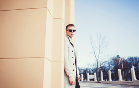 Handsome sexy man in coat posing on the street with copy space Stock Photo