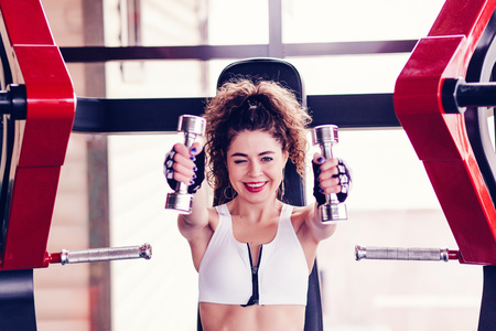 Athletic woman doing exercise for arms. Photo of fitness model working out with dumbbells in gym Stock Photo