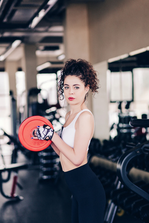 Young woman in gym working out an posing. Portrait of girl in gym.