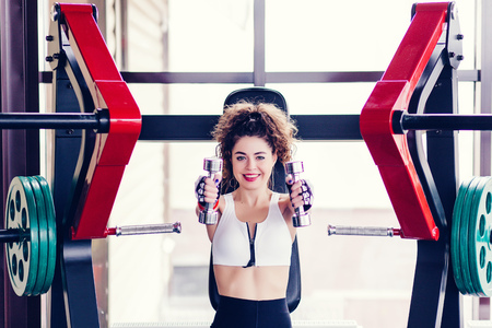 Happy sporty woman doing exercises with dumbbells in the gym Stock Photo