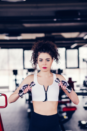 Young beautiful woman doing exercises with dumbbell in gym. fitness concept Stock Photo