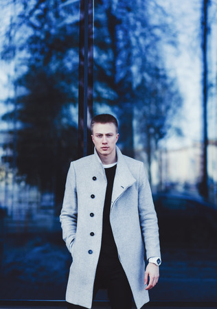 Young handsome man in stylish coat outdoors Stock Photo