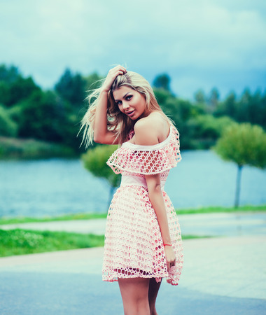 Young blonde woman in summer dress outdoors