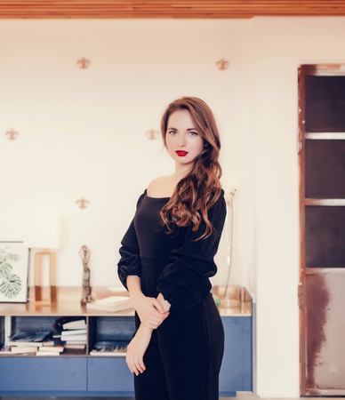 Beautiful woman in elegant black evening dress. Brunette girl Care and beauty.