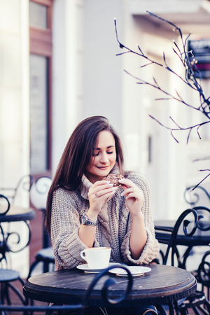 woman in sweater sitting in a cafe and holding coffee with biscuits
