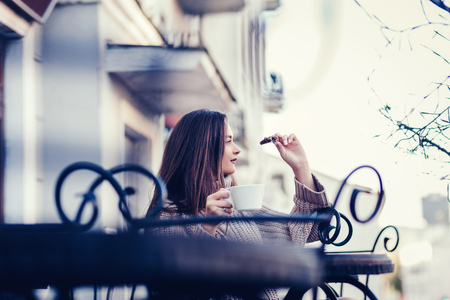 a young girl sits on the terrace of a cafe, drinking coffee with cookies