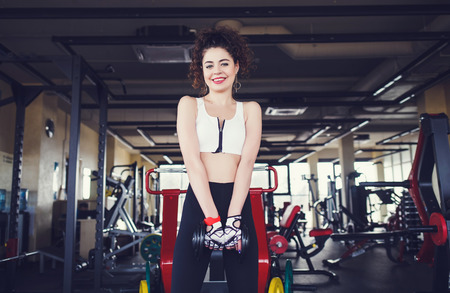 Fitness girl with dumbbell in gym