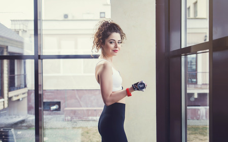 Sporty young woman with dumbbells on windows background