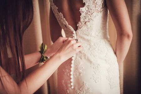 Gorgeous, bride in white dress, preparing for the wedding. Woman puts on a dress.