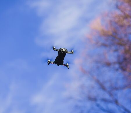 compact black drone flying in blue sky