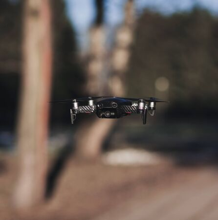 Black compact flying drone. Quadcopter with camera
