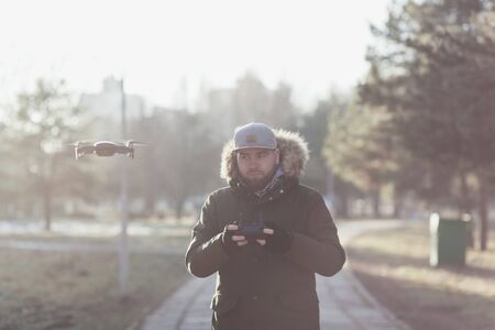young man with a beard controls a drone in a park