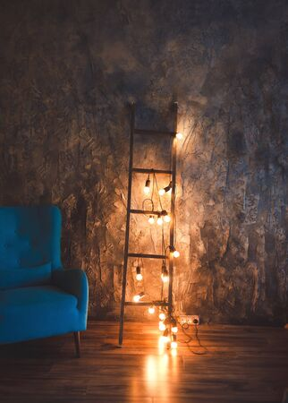 Blue chair in a dark room the bright light from lamps. Interior loft with antique walls