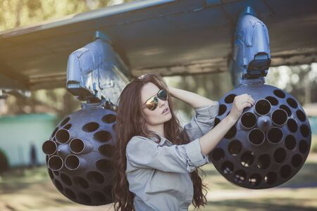 young woman poses near a military plane wearing Aviator glasses