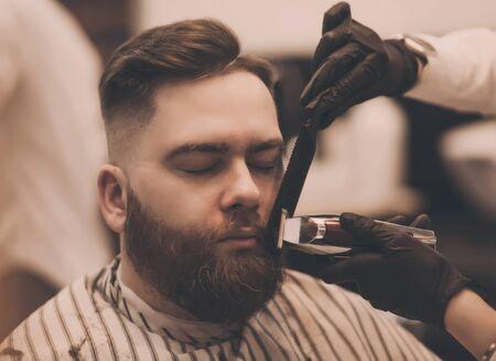 Pflege des echten Mannes. Bärtiger Mann bekommt Barthaarschnitt beim Friseur, während er im Friseursalon auf einem Stuhl sitzt