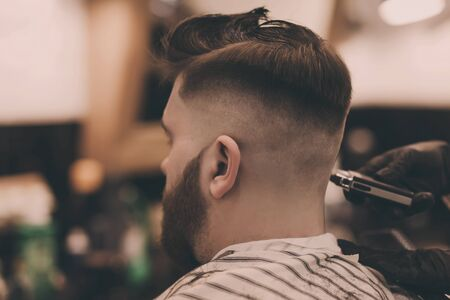 professional hairdresser cuts a mans hair in a beauty salon. Stock fotó