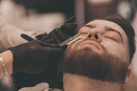 Barber in black gloves shaves a mans beard in the salon