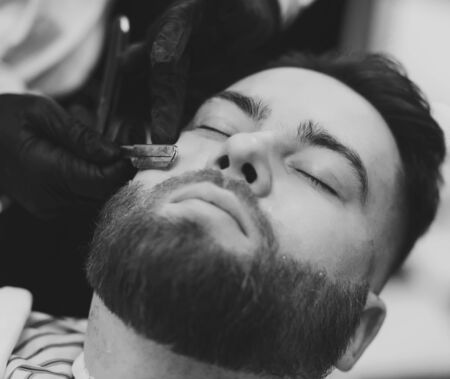close-up of barbers hands with a dangerous razor shaves a mans beard in the salon