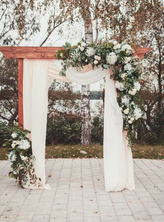 Wedding arch decorated with cloth and flowers outdoors. Beautiful wedding set up.