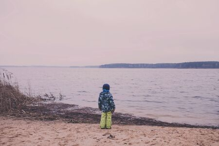 little boy stands on the shore of the lake and looks into the distance. rear view