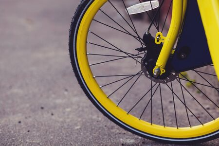 vintage yellow bicycle wheel in the city. Bicycle rentals