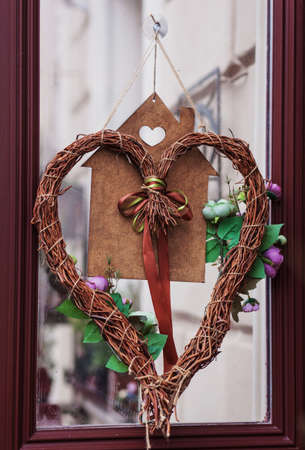 Stylish christmas wreath with red heart, modern decor on store front or building facade 免版税图像
