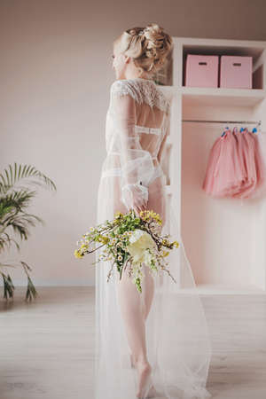 Wedding. Beautiful bride indoors with bouquet of flowers looking at camera Standard-Bild