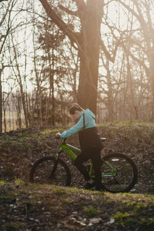Sport woman riding on bicycle on sunset forest
