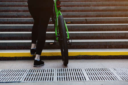 sporty woman carries a bicycle up the steps in an underground passage Stock fotó