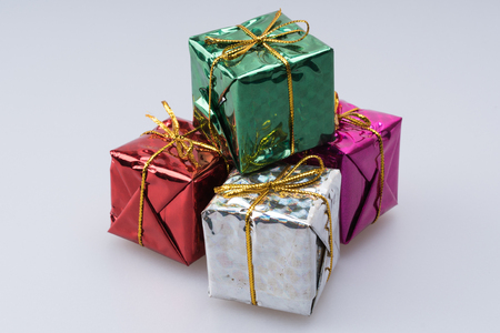 An assortment of mini gifts stacked together wrapped in shiny paper in an assortment of colors.