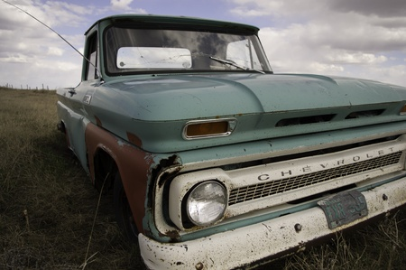 retro: Central Saskatchewan, Canada, 2010: A green classic Chevrolet pick-up truck abandoned in a field. Editorial