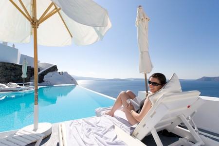 그리스 산토리니에서 수영장 근처에 앉아있는 여자 스톡 콘텐츠