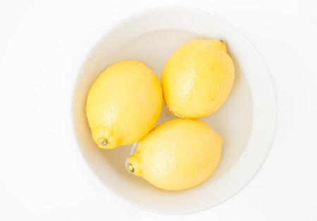 Three lemons in a white bowl