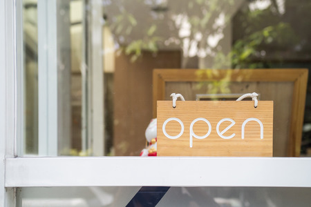 glass door: Open word on the wooden board in front of the shop Stock Photo