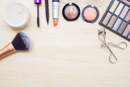 eye make up: Woman earth tone cosmetics - eyeshadow, brush on, lipstick, eye liner, mascara, powder, brush, eyelash curler. Top view with space for text.
